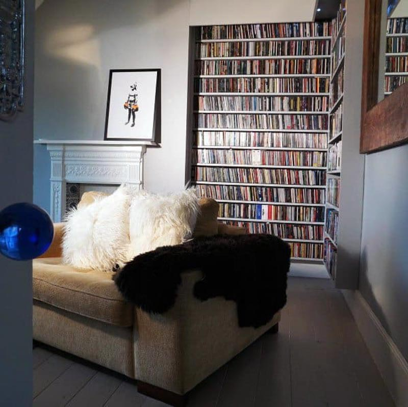 DVDs stored in classic and sophisticated built-in shelving in a Victorian style fireplace sitting room.