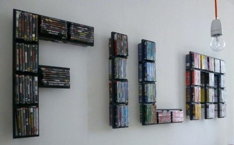 "Creative DVD storage on wall shelving in the shape of the word ""FILM."""