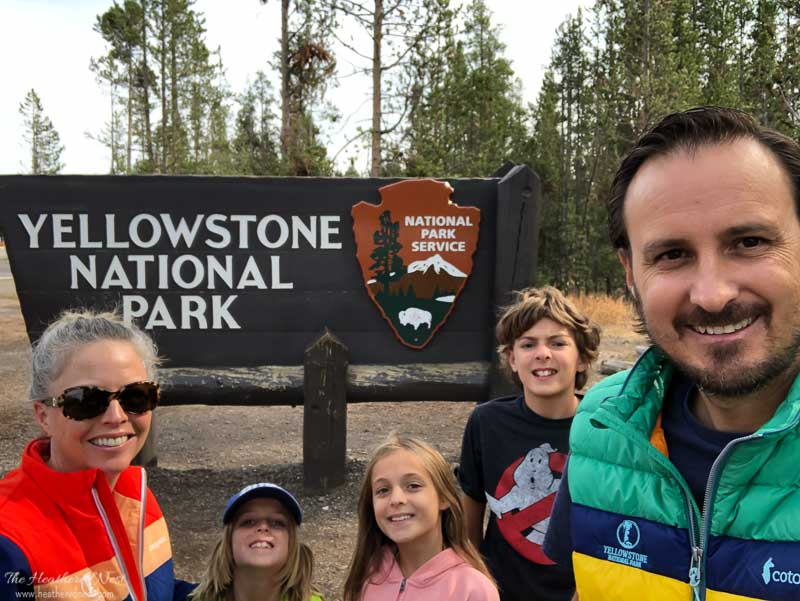 family in front of yellowstone national park sign