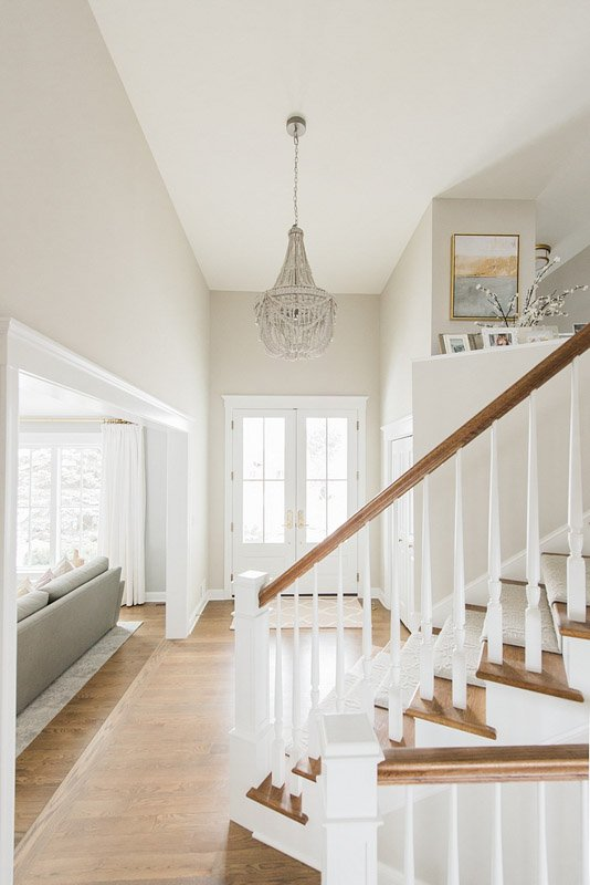 Bright, vaulted entryway with chandelier and wall paint in Benjamin Moore Sea Salt.