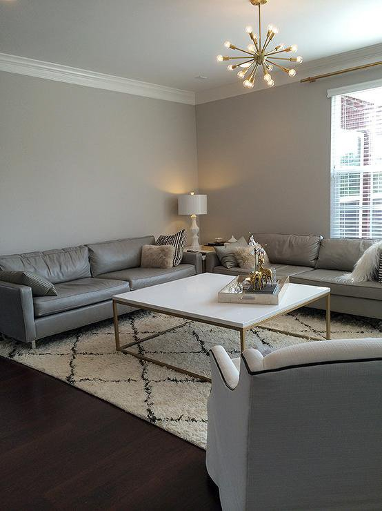 A warm gray paint on minimally decorated living room walls, with neutral furniture and a warmly lit lamp in the corner.