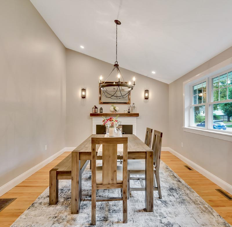 A wooden table, bench and chairs in a dining room featuring a small fireplace and Sherwin Williams Alpaca walls.