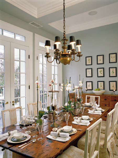 Quiet Moments paint corrals a dining room full of white trim, white recessed ceiling panels, warm, rustic wood furniture, off-white and deep brown decor accents and an antique brass chandelier.