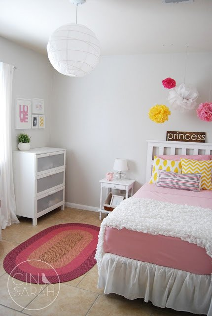 Little girl's bedroom with pale gray wall paint and pink decor accents.