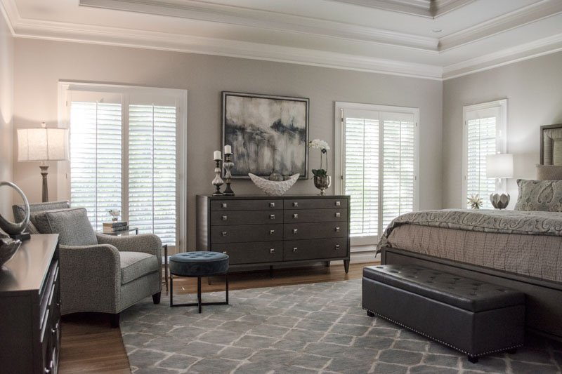 A master bedroom featuring brown tones in furniture and decor, with walls painted in Sherwin Williams Anew Gray.