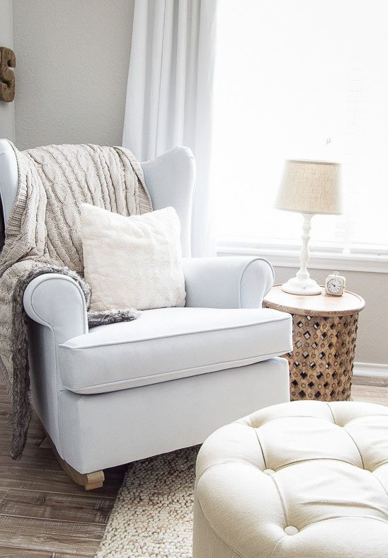 A white upholstered rocking chair and matching ottoman in a room painted in Alpaca