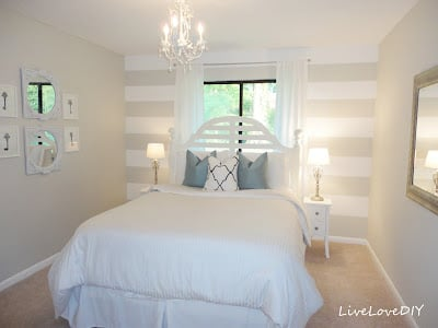 Guest bedroom with striped accent wall, white chandelier and ornate framed mirrors.