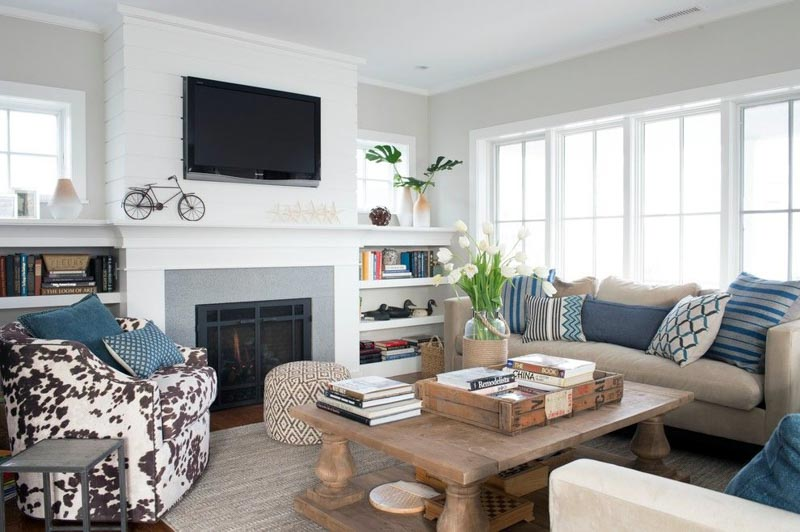 Family room with walls in Benjamin Moore Sea Salt, white brick fireplace and blue and neutral decor accents.