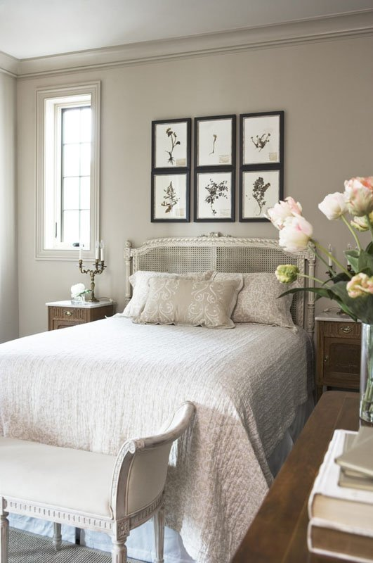 A small, neutral colored bedroom with walls and trim painted in a taupe-gray color.