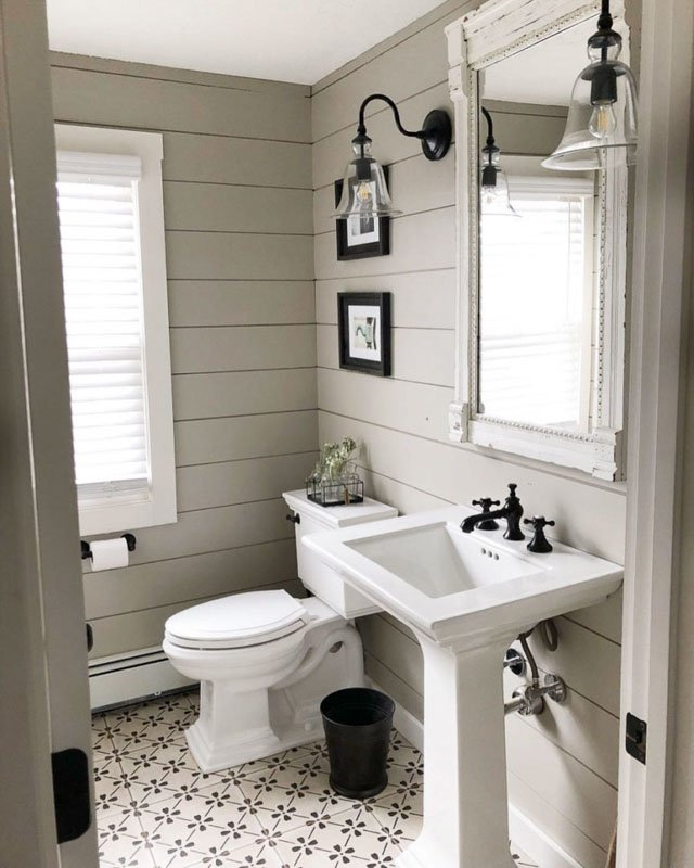 A small bathroom covered in shiplap painted in Sherwin Williams Anew Gray.
