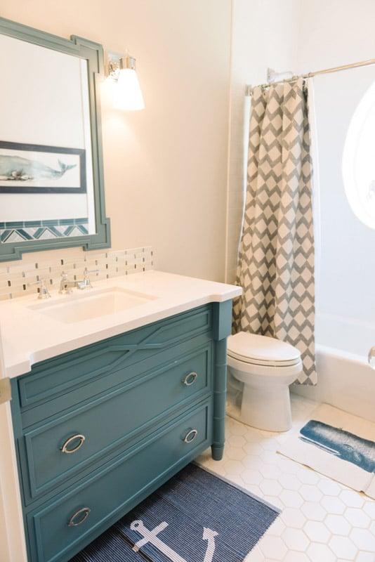 Boy's bathroom with walls painted in Benjamin Moore Sea Salt, and vanity painted in Sherwin Williams Refuge.