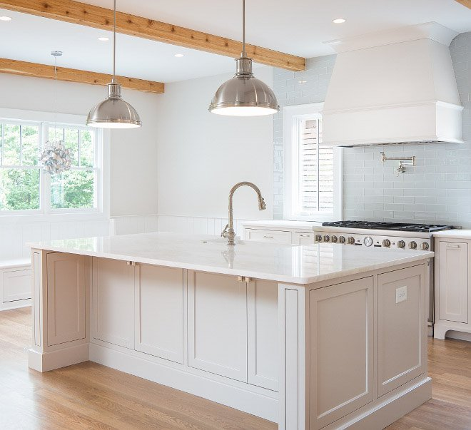 A large kitchen island with cabinets painted in a light, tan, gray paint.