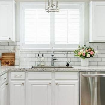 Kitchen with white cabinets, granite countertops, white subway tile backsplash and Silver Drop paint.