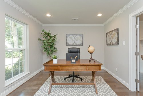 A home office space with a large window letting in a lot of light, highlighting the anew gray walls.