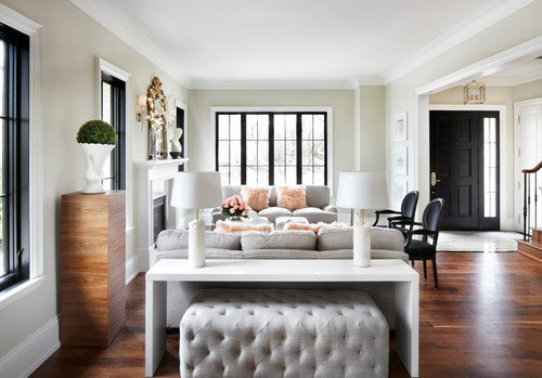 Living space with walls in BM Sea Salt paint, white trim, hardwood floors and black doors and window frames.