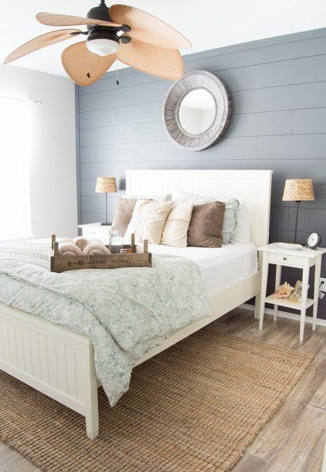 A brightly lit bedroom with a gray shiplap wall behind the bed and alpaca paint as the adjacent wall.