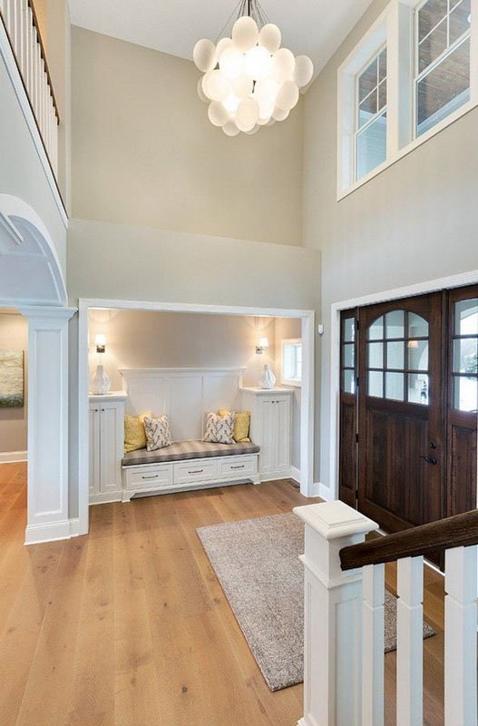 Home entry way with very high ceilings, and interior walls painted in anew gray.