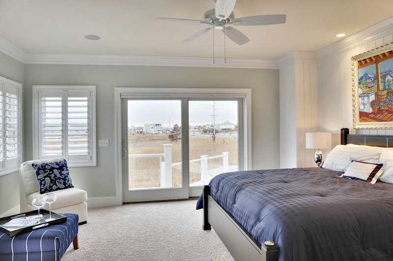 A large master suite with a tan sherwin williams paint on the walls and bright white trim around the room.