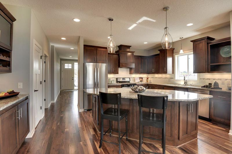 A large open kitchen concept with dark cabinets, and walls coated in Sherwin Williams Anew Gray paint.