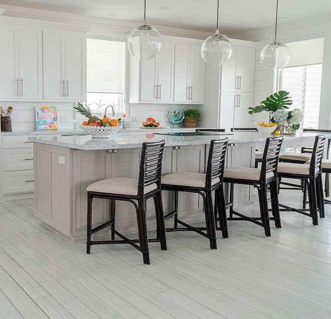 A brightly lit kitchen with a large island painted in anew gray.