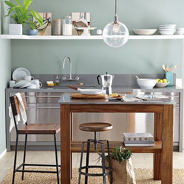 Kitchen with stainless steel appliances, wood table and benches, open shelving and wall paint in Quiet Moments.
