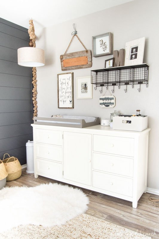 A pale warm, gray painted wall above a dresser, with rustic nursery decor.