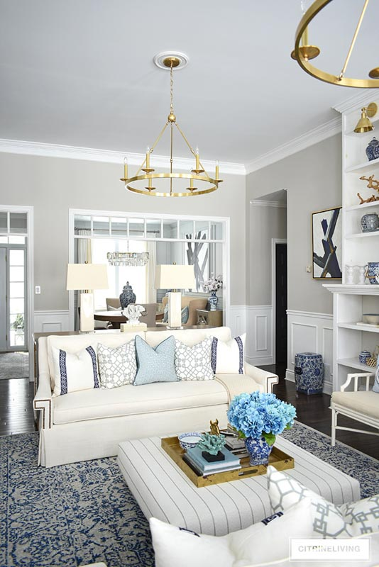 Collingwood walls and white trim are the backdrop to this living room with blue and gold decor.