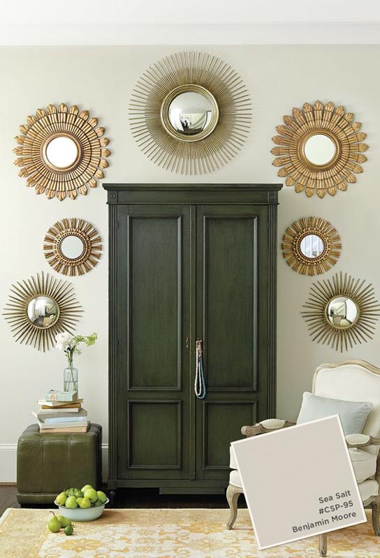 BM Sea Salt paint color on the walls, dark green wardrobe and gold sun mirror accents.