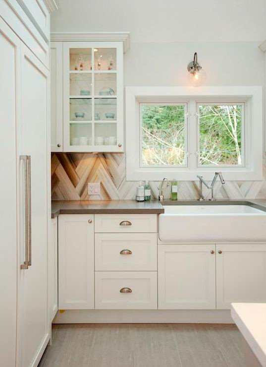 This contemporary-meets-farmhouse kitchen features white glass-front cabinets, taupe countertops and a unique chevron backsplash.