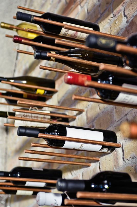 dowels or capped copper pipes in brick wall to create wine storage feature wall