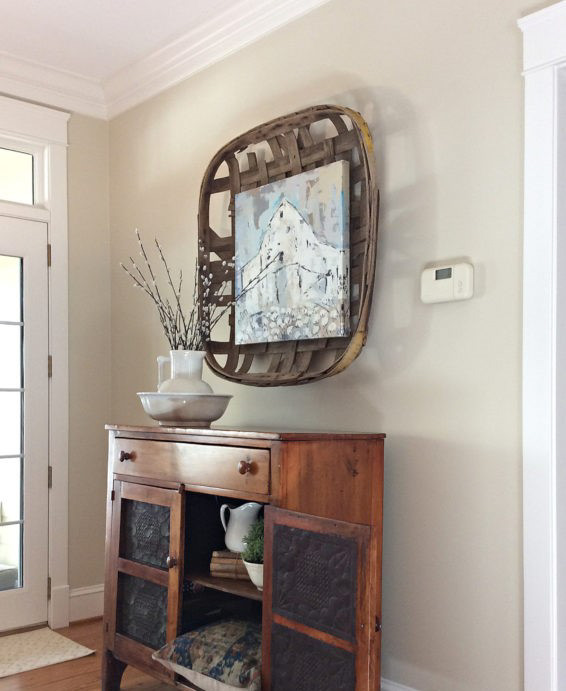 An entryway with a vintage cabinet and decor, with Manchester Tan walls by Benjamin Moore.