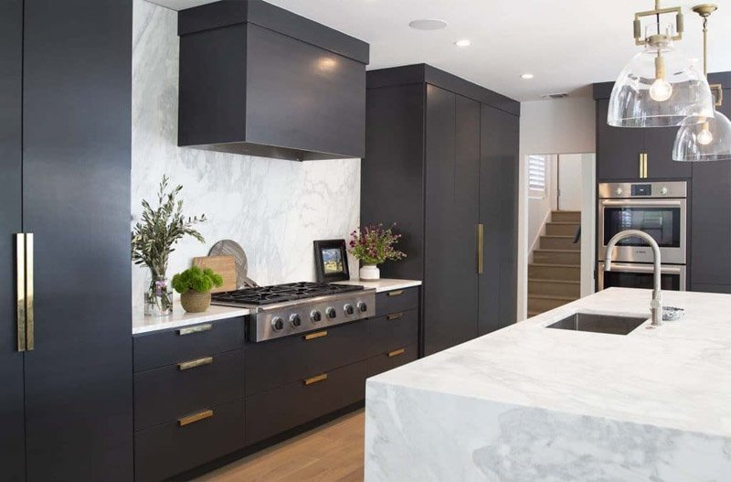 Large flat black painted cabinets with gold cabinet and drawer pulls.