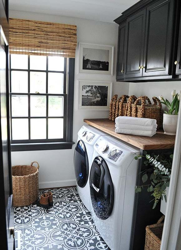 Black painted wIndow seals and cabinetry of a farmhouse meets modern laundry room.