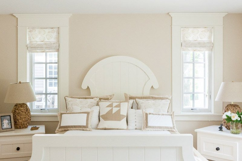 A sunny bedroom with white wood bed frame, side tables and window trim, and tan walls as a backdrop.