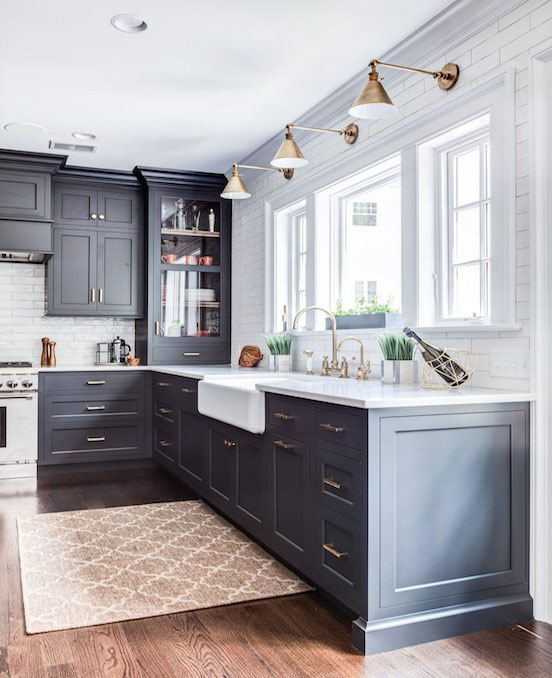 A farmhouse style kitchen with painted black drawers and cabinets and modern pulls.