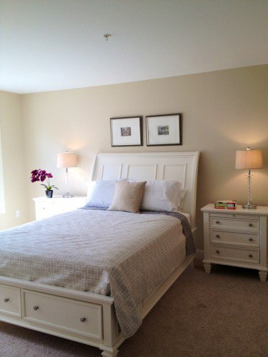 A staged bedroom in a home with BM Manchester Tan walls.