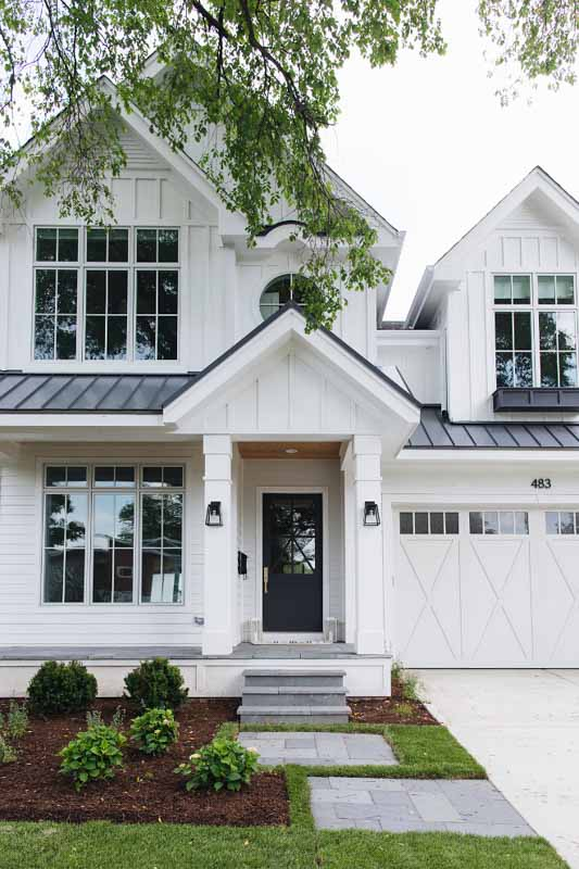 A charcoal black accent painted door on a bright white home.