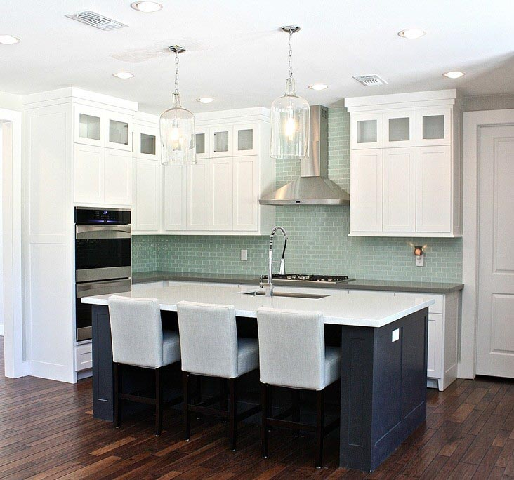 A kitchen island painted in Wrought Iron paint alongside white perimeter cabinets.