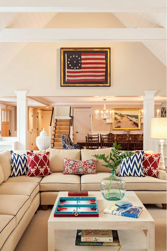 Benjamin Moore Manchester Tan living room with a cozy couch covered in red, white and blue colored pillows.