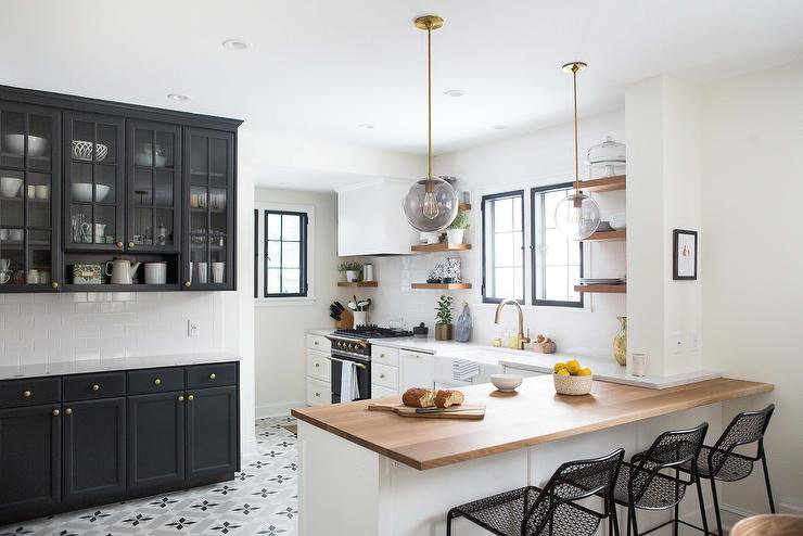 Glass front cabinet doors painted black int he midst of other white cabinets with light wooden accents.