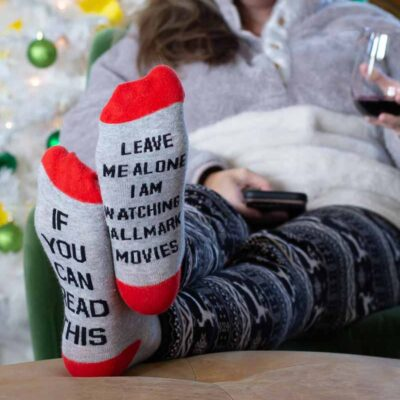 """woman sitting in chair with wine by christmas tree - socks say """"if you can read this leave me alone I'm watching Hallmark movies"""""""