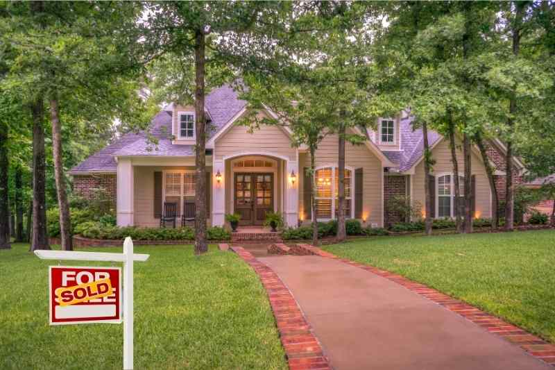 how long does it take to sell a house? beautiful home with sold sign in front yard