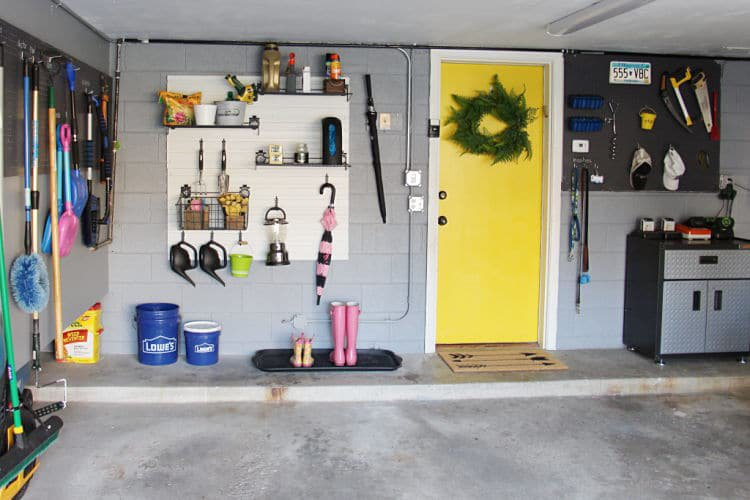 Garage storage with pegboard on both sides of a yellow door