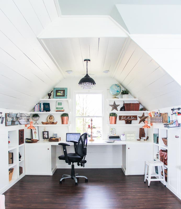 Attic filled with built in shelves and a desk