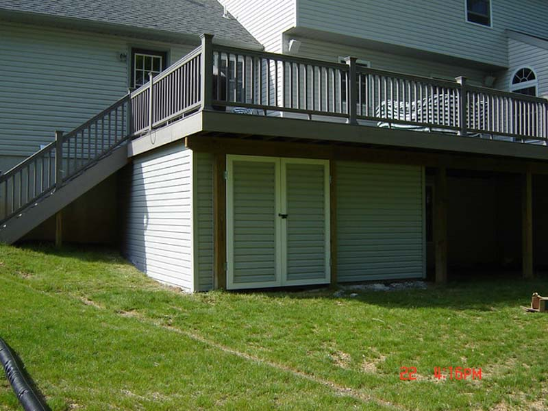 concealed storage shed under deck clad with siding