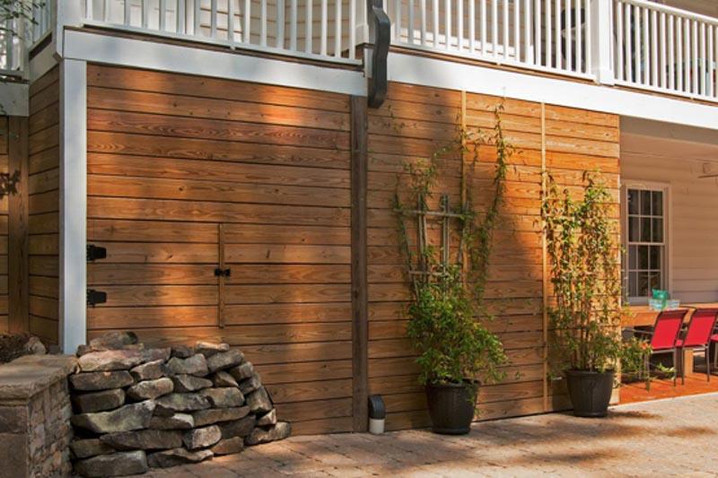 wood clad siding under deck hides storage areas