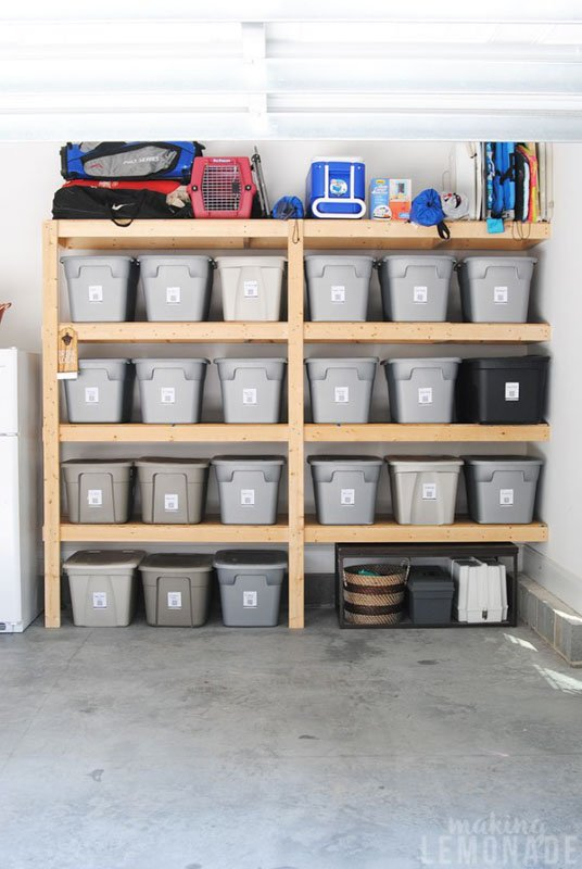 Wooden garage shelving filled with gray plastic tubs