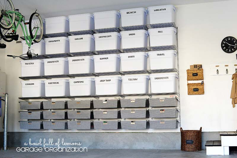 A wall filled with garage storage in metal drawers and white bins