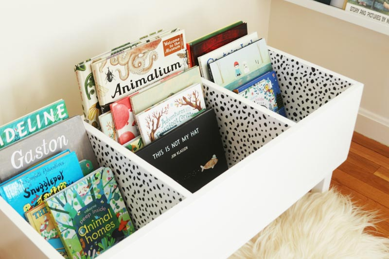 A DIY book bin painted white and covered in polka-dotted wallpaper.
