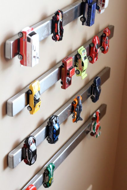 Magnetic knife strips mounted on a wall, being used as hot wheel car storage.